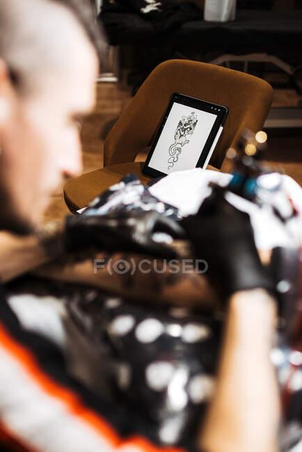 Von oben stilvolle Mann mit Piercing mit Tätowiermaschine, um Tätowierung auf Bein der Ernte Kunden während der Arbeit im Salon zu machen — Stockfoto
