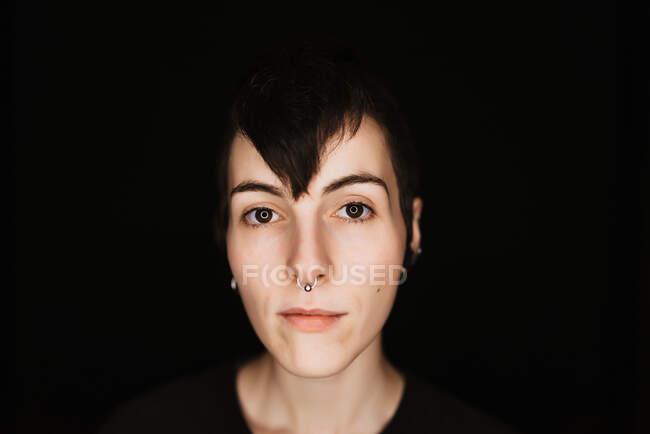 Современная модная женщина с короткими волосами и пирсингом в носу, смотрящая на камеру на черном фоне — стоковое фото