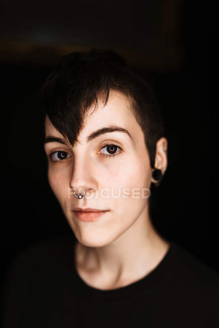 Modern trendy female with short hair and piercing in nose looking at camera against black background — Stock Photo