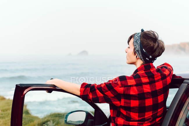 Вид на спокойную женщину-хипстера с пирсингом в повседневной рубашке и бандане, стоящей рядом с машиной и смотрящей на пустое море — стоковое фото