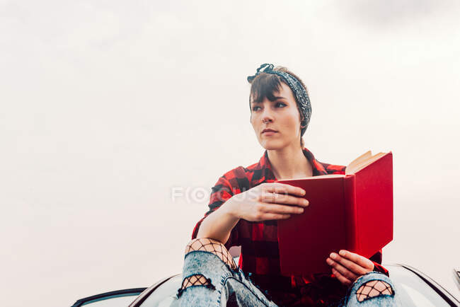 Thoughtful casual woman with book at seashore — Stock Photo