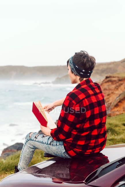 На задньому плані - безлика екстравагантна леді в повсякденному одязі і бандана, що сидить на капоті автомобіля і читає книгу на порожньому морі. — стокове фото
