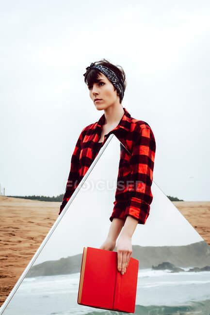 Серьёзная задумчивая молодая женщина в непринужденной красной и черной клетчатой рубашке, стоящая на песчаном пляже с красной книгой в руке и большим зеркалом с морским и скальным отражением — стоковое фото