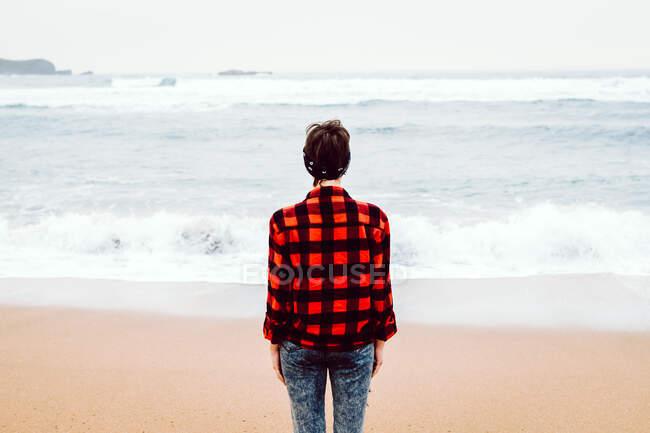 Женщина, стоящая на мокром песке на пляже — стоковое фото