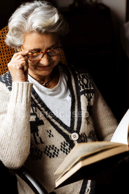 Elderly woman reading by window with enthusiasm — Stock Photo