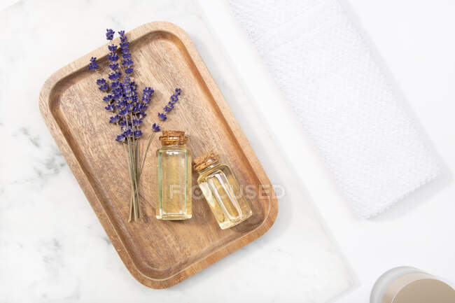Top view lavender flower and its essential oil on a bottle at a marble table on wooden tray — Stock Photo