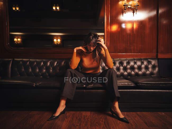 Mujer pensativa de moda en ropa elegante sentada piernas separadas en el sofá de cuero negro con la cabeza hacia abajo en el gabinete - foto de stock