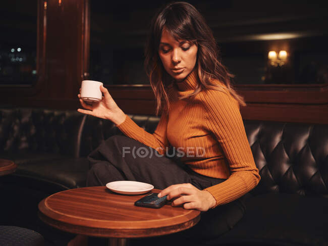 Умная женщина, удобно сидящая за круглым столом и серфингующая мобильный телефон — стоковое фото
