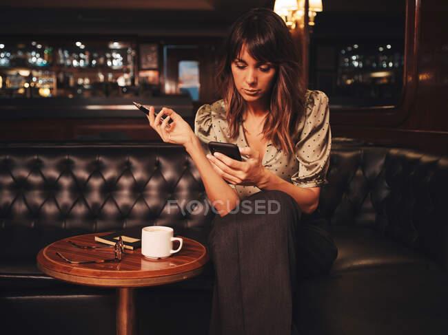Une femme élégante réfléchie surfant sur un téléphone portable tenant un stylo pour écrire confortablement assis à une table ronde en bois avec café — Photo de stock