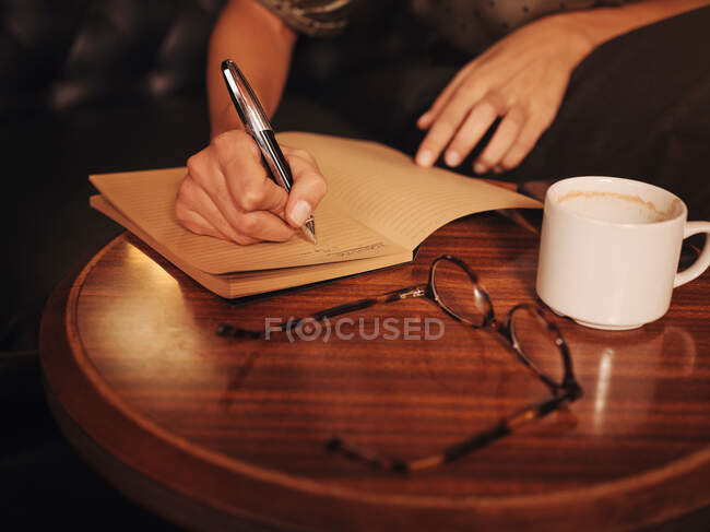 From above crop unrecognizable woman writing with pen in notebook at round wooden table with coffee and glasses in cafe — Stock Photo