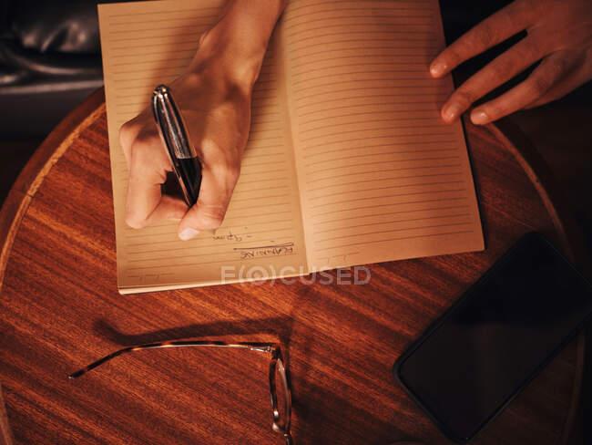 De cima cultura mulher irreconhecível escrevendo com caneta no caderno em mesa de madeira redonda com telefone celular e óculos no café — Fotografia de Stock