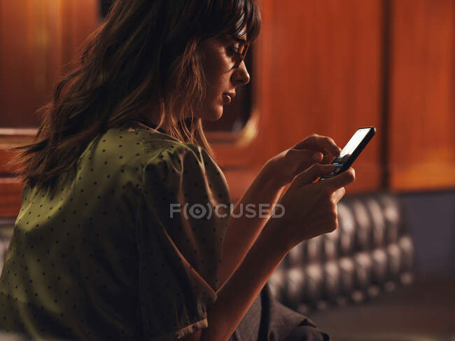 Side view of stylish thoughtful woman surfing mobile phone comfortable sitting at black leather sofa in cafe — Stock Photo