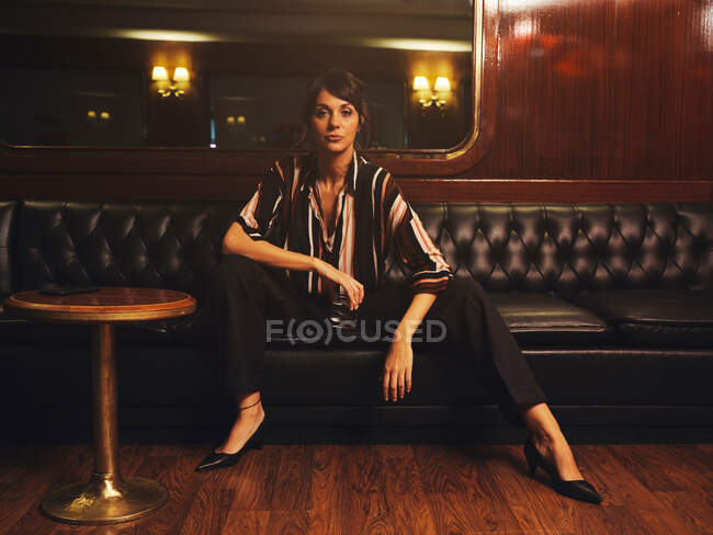 Fashionable stylish woman in trendy clothes sitting wide spread apart legs on black leather couch and looking at camera — Stock Photo