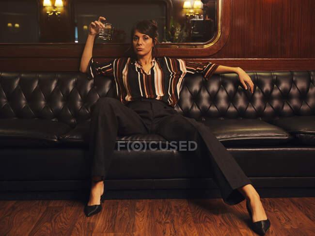Mujer con estilo de moda en ropa de moda sosteniendo vidrio de alcohol sentado de par en par las piernas separadas en el sofá de cuero negro y mirando a la cámara - foto de stock