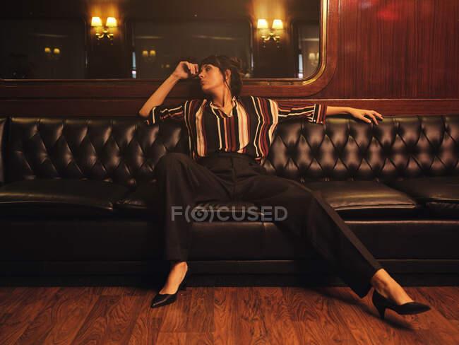 Mujer elegante de moda en ropa de moda sentada piernas separadas en el sofá de cuero negro y mirando hacia otro lado - foto de stock