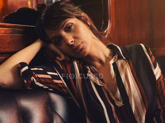 Fashionable stylish woman in trendy clothes sitting on black leather couch and looking at camera — Stock Photo