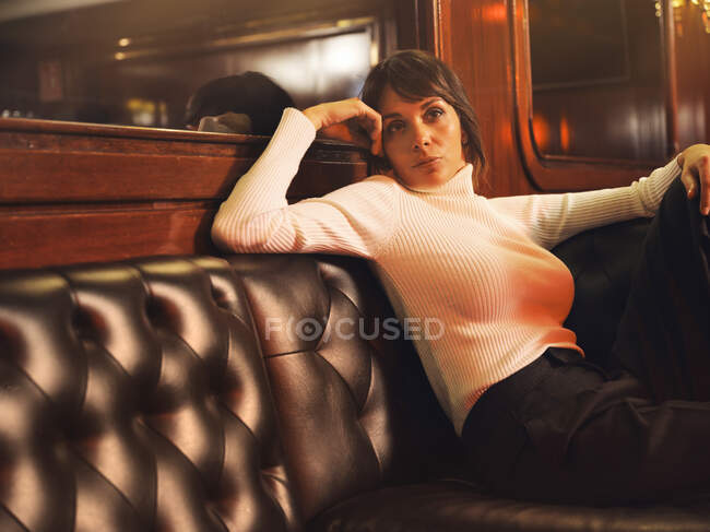 Fashionable stylish woman in trendy clothes sitting on black leather couch and looking away — Stock Photo