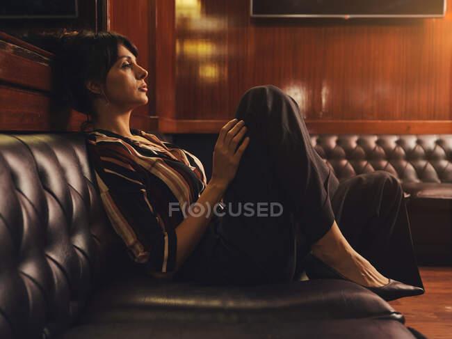 Дивна жінка в модному одязі сидить на чорному шкіряному дивані і озирається — стокове фото