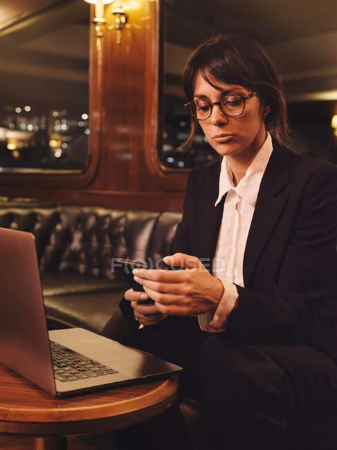 Умная бизнес-леди в очках, сидящая на ноутбуке и проверяющая информацию в мобильном телефоне, уютно сидит на черном кожаном диване в кафе — стоковое фото