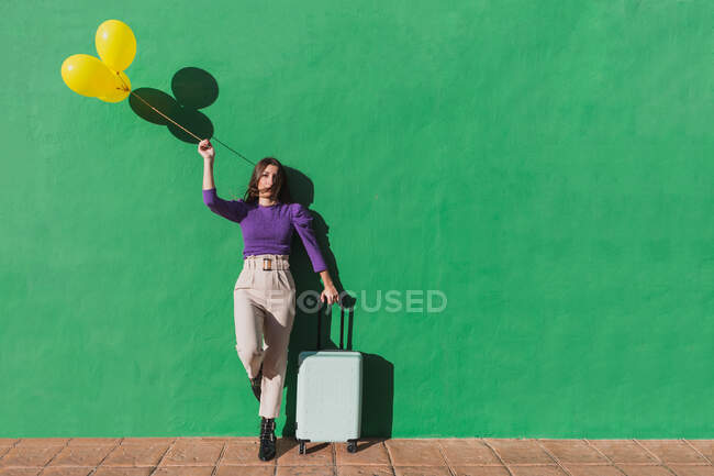 Modern fashionable carefree female holding bunch of yellow balloons and suitcase while standing against green wall in sunny day — Stock Photo