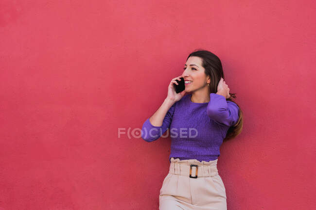 Positive young female in violet blouse and light beige pants talking on mobile phone while standing against colorful red wall background — Stock Photo
