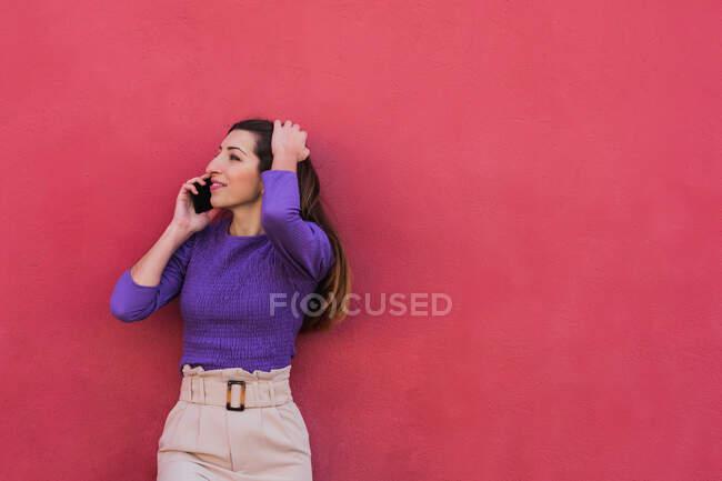 Jeune femme positive en chemisier violet et pantalon beige clair parlant sur téléphone portable tout en se tenant debout sur fond de mur rouge coloré — Photo de stock