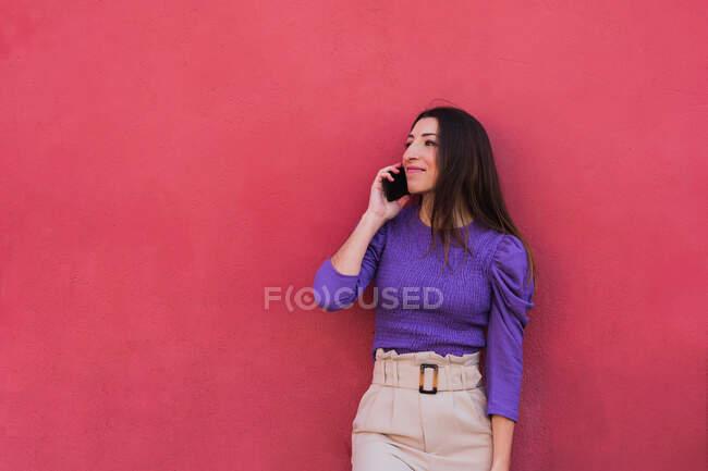 Позитивная молодая женщина в фиолетовой блузке и светло-бежевых брюках разговаривает по мобильному телефону, стоя на фоне красочной красной стены — стоковое фото