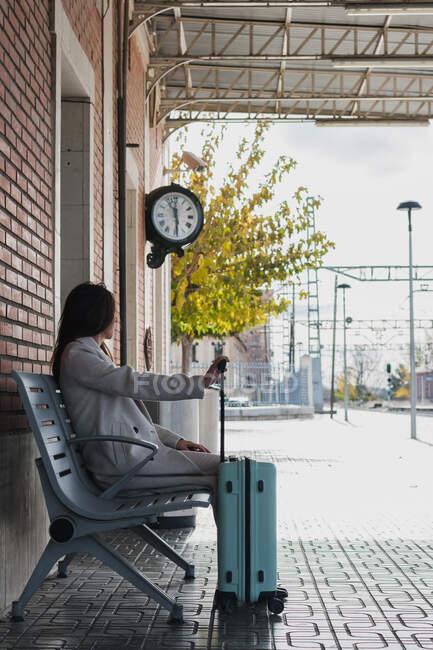 Vue latérale d'une jeune voyageuse élégante avec une valise assise sur un banc et attendant le transport à la gare par temps ensoleillé — Photo de stock