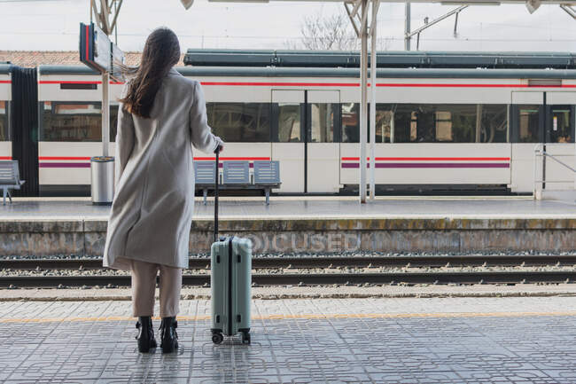 Back view of unrecognizable female traveler in stylish outfit standing with suitcase on platform of railway station — Stock Photo