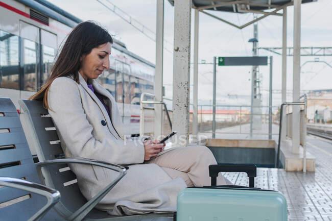 Vista laterale del viaggiatore femminile moderno con valigia seduta sulla panchina sul marciapiede della stazione ferroviaria e con smartphone in attesa del treno — Foto stock