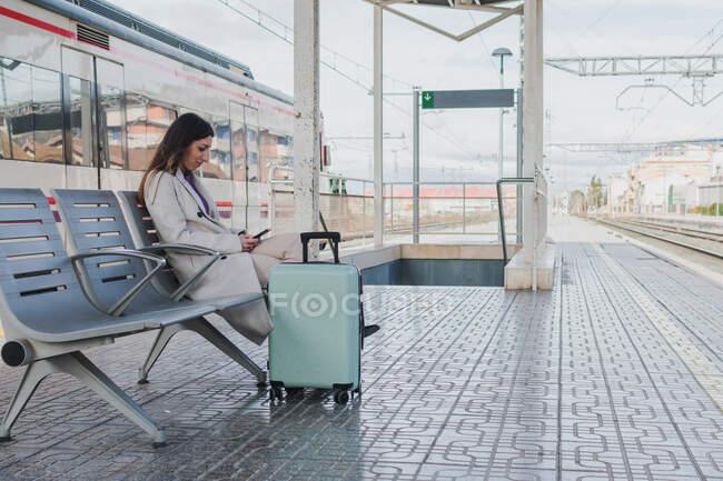 Vista lateral do viajante moderno feminino com mala sentada no banco na plataforma da estação ferroviária e usando o smartphone enquanto espera pelo trem — Fotografia de Stock