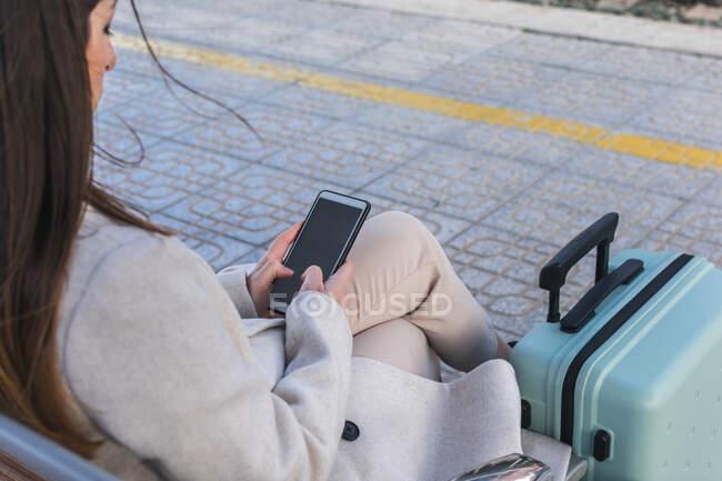 Сверху лопнула неузнаваемая путешественница с чемоданом, сидящим на скамейке на платформе железнодорожного вокзала и пользующимся смартфоном в ожидании поезда — стоковое фото