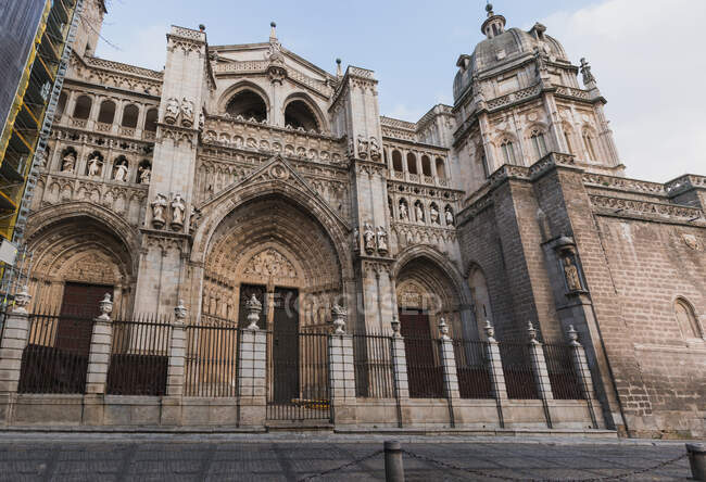 From below of exterior of beautiful medieval Gothic styled stone building of Primate Cathedral of Saint Mary of Toledo in Spain against blue cloudy sky — Stock Photo