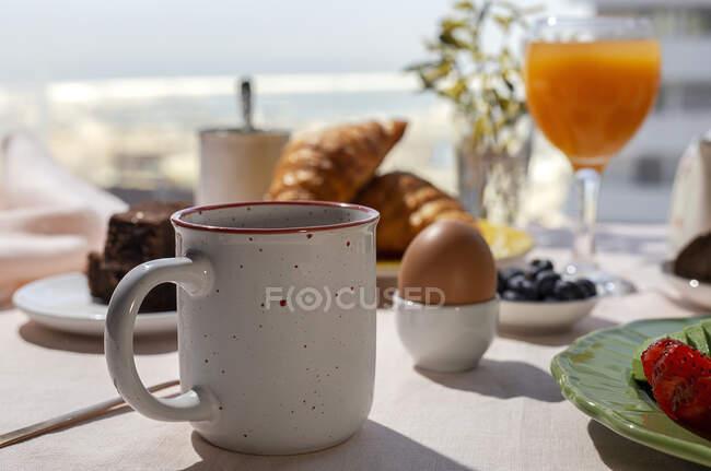 Домашний завтрак на завтрак в солнечном свете с приготовленными яйцами, черникой, бисквитом, круассанами, тостами, чаем, кофе и апельсиновым соком — стоковое фото