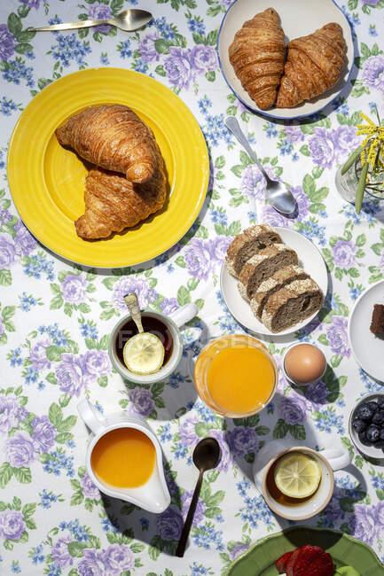 Dall'alto vista del brunch completo fatto in casa colazione alla luce del sole con uova cotte, mirtilli, pan di Spagna, croissant, toast, tè, caffè e succo d'arancia — Foto stock