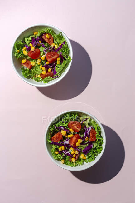 Salade de laitue fraîche avec tomates cerises, oignons rouges et maïs, lumière du soleil sur fond rose venant d'en haut. Aliments sains. Nourriture végétale. — Photo de stock