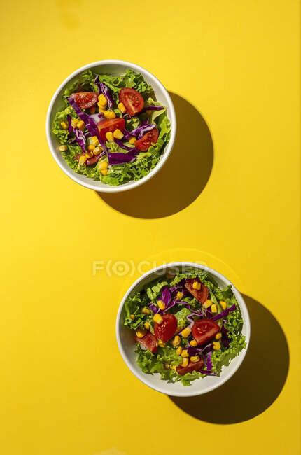 Ensalada de lechuga fresca con tomates de cerezas, cebolla roja y maíz, luz solar sobre fondo rosa desde arriba. Comida saludable. Comida vegana . - foto de stock