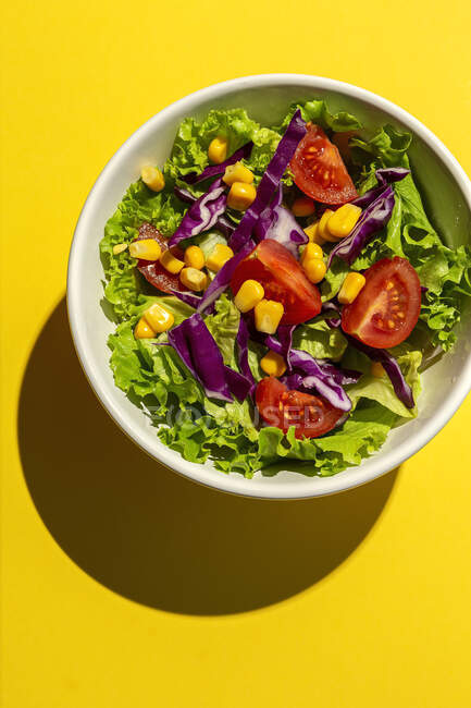 Fresh lettuce salad with Cherries tomatoes, red onion and corn, sunlight on pink background from above. Healthy food. Vegan food. — Stock Photo