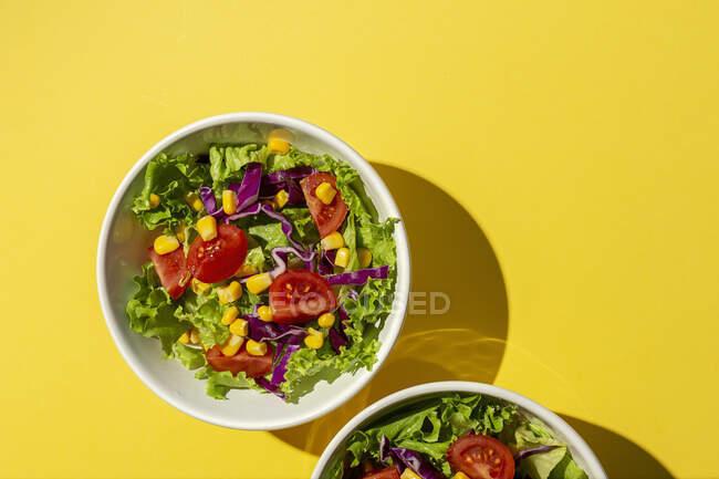 Salada de alface fresca com tomate cereja, cebola vermelha e milho, luz solar em fundo rosa de cima. Comida saudável. Comida Vegan . — Fotografia de Stock