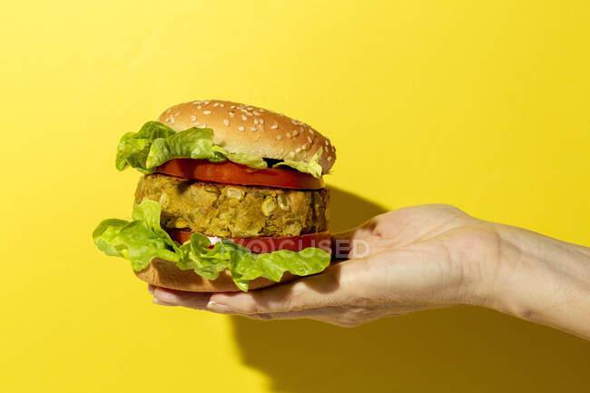 Cortada mano irreconocible persona sosteniendo una hamburguesa de lenteja verde vegana casera con tomate, lechuga y papas fritas sobre un fondo colorido amarillo - foto de stock