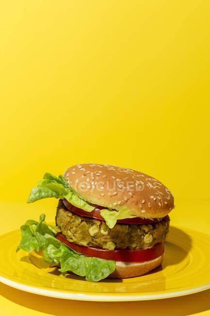 Hausgemachter veganer grüner Linsenburger mit Tomaten, Salat und Pommes auf gelbem Hintergrund — Stockfoto
