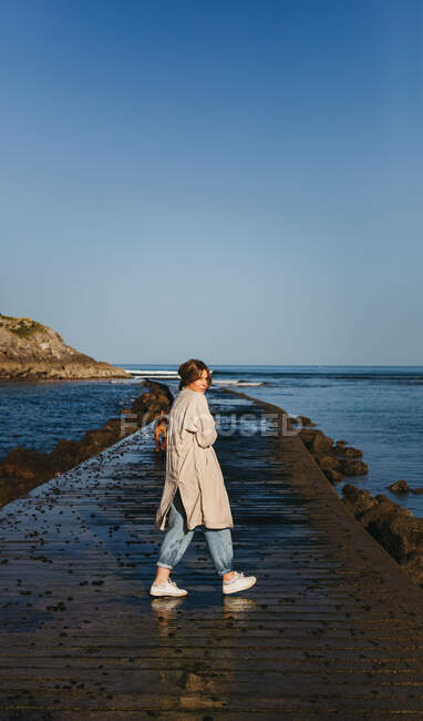 Female in casual clothes and big brown Mastiff dog looking at camera smiling while walking along wet wooden pier against calm bay water under blue sky in Spain — Stock Photo