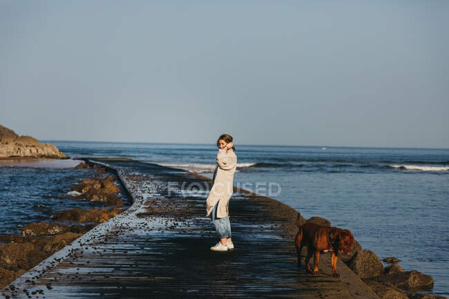 Side view of woman traveler in casual clothes walking along wet wooden pier against sea waves and rocky shore in Spain — Stock Photo