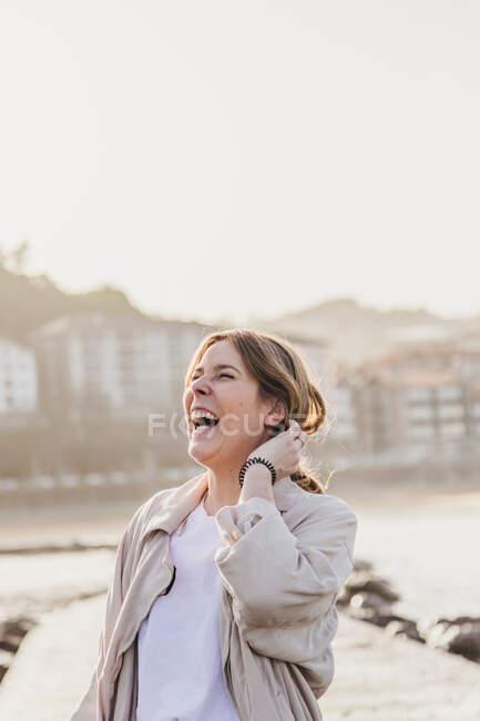 Mulher loira feliz em roupas casuais com os olhos fechados rindo enquanto estava em pé no cais e tocando o cabelo contra o ambiente urbano turvo da cidade resort na Espanha — Fotografia de Stock