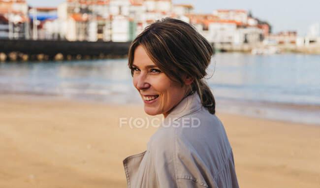 Mulher loira feliz em roupas casuais olhando para a câmera rindo enquanto estava de pé no cais e tocando o cabelo contra o ambiente urbano turvo da cidade resort na Espanha — Fotografia de Stock