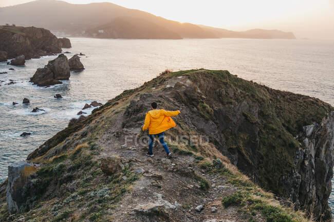 Vue arrière d'un homme méconnaissable en veste jaune vif et en denim courant sur une colline rocheuse et profitant d'un paysage pittoresque de la côte de la mer pendant le coucher du soleil en Espagne — Photo de stock