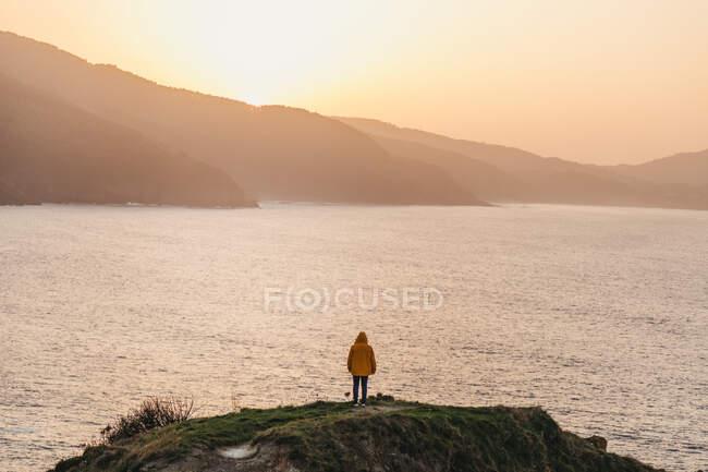 Обратный вид на неузнаваемого человека в яркой желтой куртке и джинсе, стоящего на скалистом холме и наслаждающегося живописными пейзажами морского побережья во время заката в Испании — стоковое фото