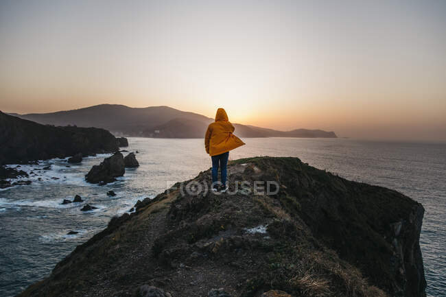 Back view of unrecognizable man in vibrant yellow jacket and denim standing on rocky hill and enjoying picturesque scenery of sea coast during sunset in Spain — Stock Photo