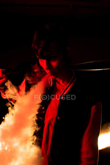 Contemporary female in bomber jacket holding a black baseball bat on shoulder while smoking with red light on background — Stock Photo
