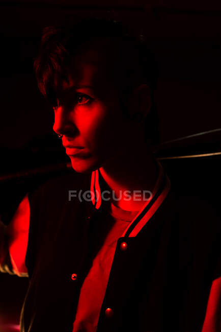Side view of contemporary female in bomber jacket looking away holding a black baseball bat with red light on background — Stock Photo